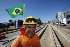Trabalhador posa com bandeira do Brasil em linha de VLT sendo construída em Cuiabá. 11/6/2014  REUTERS/Eric Gaillard