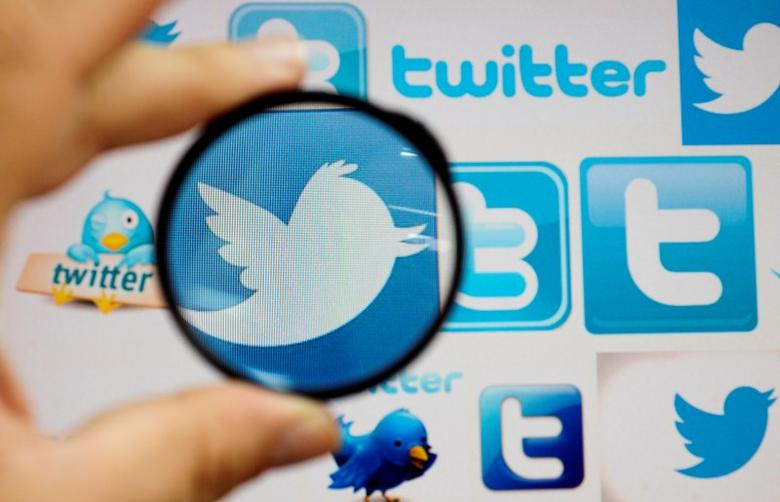 A person holds a magnifying glass over a computer screen displaying Twitter logos, in this picture illustration taken in Skopje September 10, 2013.  REUTERS/Ognen Teofilovski/Files
