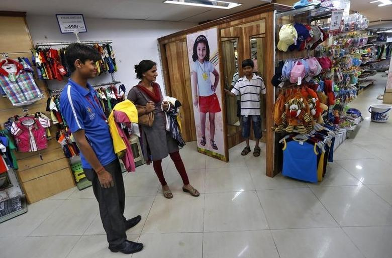 A boy stands inside a fitting room as his mother and a salesman (L) look on inside a retail store in New Delhi April 6, 2013. REUTERS/Adnan Abidi/Files