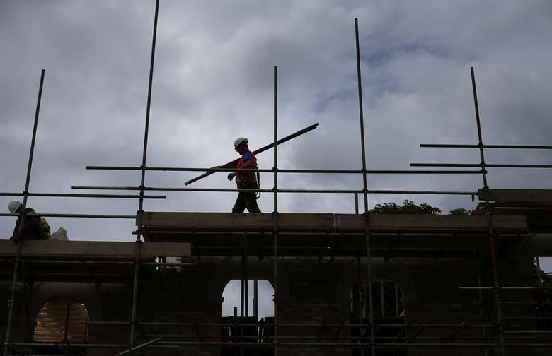 A builder assembles scaffolding as he works on new homes being built for private sale on a council housing estate, in south London June 3, 2014. REUTERS/Andrew Winning