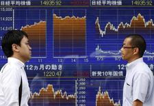Peatones pasan por una pantalla electrónica que muestra el gráfico reciente de las fluctuaciones del promedio del Nikkei en Tokio. 2 de junio de 2014.  Las bolsas de Asia cedían el viernes y el petróleo alcanzó máximos en nueve meses luego de que una escalada de la violencia en Irak redujo el apetito de riesgo que había sido sólido pocos días atrás. REUTERS/Yuya Shino