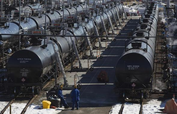 Irving Oil workers inspect rail cars carrying crude oil at the Irving Oil rail yard terminal in Saint John, New Brunswick in this March 9, 2014 file photo. CREDIT: REUTERS/DEVAAN INGRAHAM/FILES
