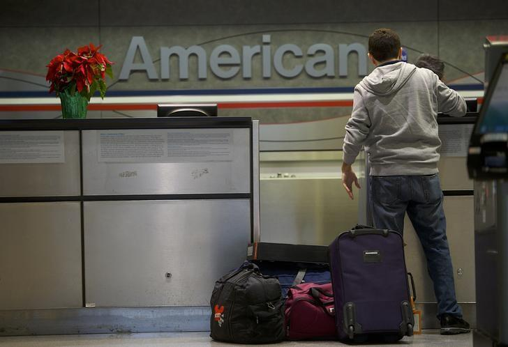 A man checks in his luggage at the American Airlines check-in counter at Philadelphia International Airport in Philadelphia, Pennsylvania on December 9, 2013.  REUTERS/Mark Makela