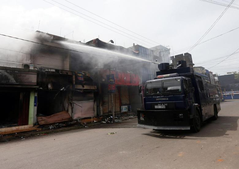 A police vehicle sprays water from a water cannon on a burnt shop after a clash between Buddhists and Muslims in Aluthgama June 16, 2014.  REUTERS/Dinuka Liyanawatte