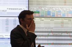 Мужчина на фоне экрана с котировками на ММВБ в Москве 1 июня 2012 года.  Торги российскими акциями начались в среду с несущественного повышения основных индексов после снижения накануне.  REUTERS/Sergei Karpukhin