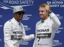 Mercedes Formula One driver Nico Rosberg of Germany (R) and teammate Lewis Hamilton of Britain react after qualifying first and second (respectively) for the race during the qualifying session of the Canadian F1 Grand Prix at the Circuit Gilles Villeneuve in Montreal June 7, 2014. REUTERS/Mathieu Belanger