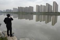 Un hombre habla por su celular cerca de un complejo habitacional en Taiyuan, 11 de mayo de 2014. Los precios promedio de las viviendas en China cayeron en mayo por primera vez en dos años y debilidad de los precios se extendió a más ciudades importantes, lo que se suma a otras señales de enfriamiento en el mercado inmobiliario que plantean un riesgo cada vez mayor para la economía en general. REUTERS/Jon Woo