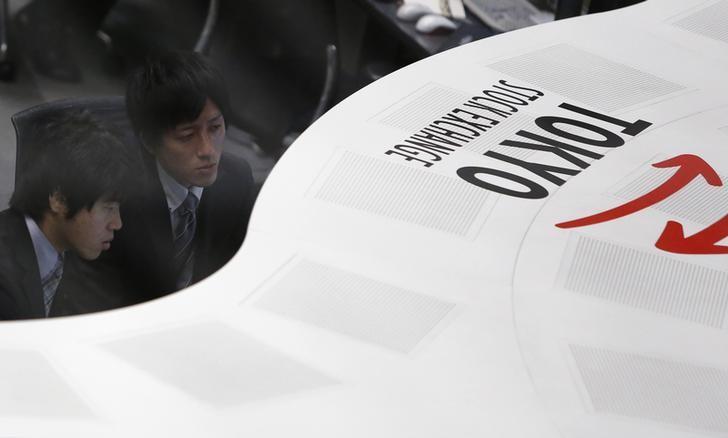 Tokyo Stock Exchange (TSE) staff members work at the bourse at TSE in Tokyo November 14, 2013. REUTERS/Yuya Shino