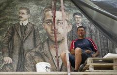 A worker smokes a cigarette in front of a mosaic with image of Gavrilo Princip, in Andricgrad village near Visegrad June 19, 2014. REUTERS/Djordje Kojadinovic
