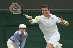 Milos Raonic of Canada hits a return to Jack Sock of the U.S. during their men's singles tennis match at the Wimbledon Tennis Championships, in London June 26, 2014.                REUTERS/Stefan Wermuth