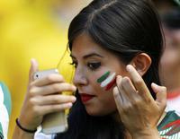 """En la imagen, una aficionada de México mira el móvil en Fortaleza el 29 de junio de 2014.  Con 1.000 millones de posteos, """"me gusta"""" y comentarios apenas en la primera mitad de la competencia, el Mundial es el evento más compartido en los 10 años de historia de Facebook, según datos de la red social a los que Reuters tuvo acceso. REUTERS/Marcelo Del Pozo"""