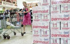 Imagen de archivo de productos de Parmalat a la venta en un supermercado en Rio de Janeiro, mientras una compradora pasa cerca de los cartones de leche durante la crisis, 4 de febrero de 2004. El índice de confianza de servicios de Brasil retrocedió un 0,7 por ciento en junio respecto a mayo, en su cuarto mes consecutivo a la baja, dijo el martes la privada Fundación Getulio Vargas (FGV). REUTERS/Bruno Domingos/Files