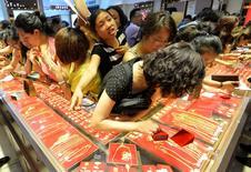 Clientes discuten por ver accesorios de oro en una tienda en descuento en Taiyuan, 6 de julio de 2013.  Aunque la economía de China está operando dentro de un rango razonable y algunos índices están demostrando una tendencia positiva, la presión bajista todavía existe, dijo el miércoles el primer ministro del país asiático, Li Keqiang. REUTERS/Jon Woo