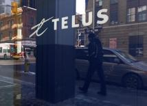 A pedestrian is reflected in the window of a Telus store while using a mobile phone in Ottawa February 11, 2011.   REUTERS/Chris Wattie