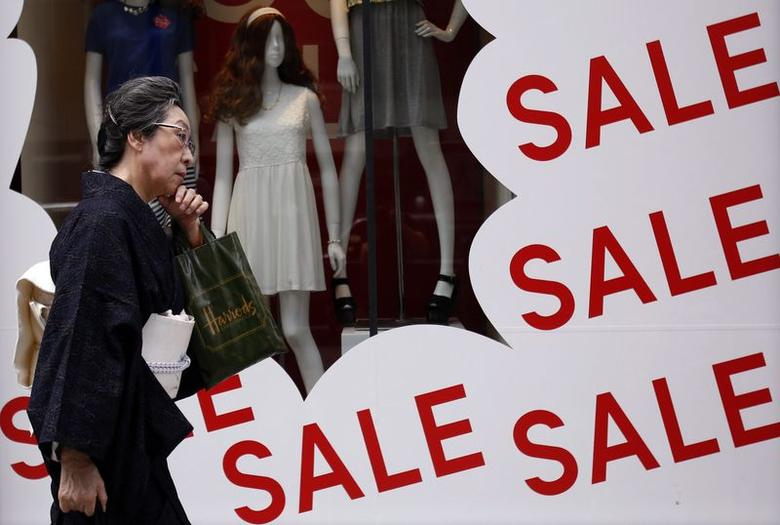 A woman in a kimono walks past a store advertising a sale at a shopping district in Tokyo June 26, 2014. REUTERS/Yuya Shino