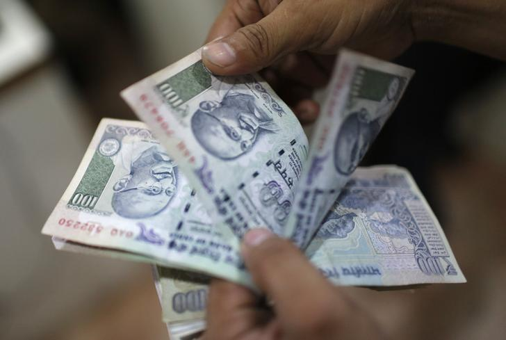 An employee counts rupee notes inside a private money exchange office in New Delhi July 5, 2013. REUTERS/Adnan Abidi/Files