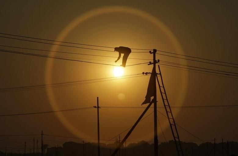 An employee from the electricity board works on newly installed overhead power cables in Allahabad December 7, 2012. REUTERS/Jitendra Prakash/Files