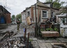 Сотрудник украинской полиции прикрывает работающих саперов в поселке Семеновка под Славянском 14 июля 2014 года. По меньшей мере 1.129 человек были убиты и 3.442 ранены с середины апреля на востоке Украины, где украинская армия три месяца воюет с вооруженными сепаратистами, говорится в четвертом ежемесячном докладе ООН, обнародованном в понедельник. REUTERS/Gleb Garanich