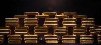 Слитки золота в хранилище  ProAurum в Мюнхене 6 марта 2014 года. Цены на золото стабильны чуть ниже $1.300 за унцию и снизятся второй месяц из трех последних за счет оптимизма в отношении американской экономики. REUTERS/Michael Dalder