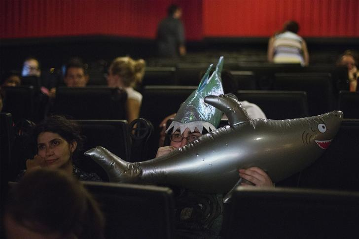 An audience member wearing a shark themed hat blows up an inflatable shark while attending a midnight screening of the U.S. cable television network Syfy film ''Sharknado'' in New York, August 2, 2013. REUTERS/Lucas Jackson