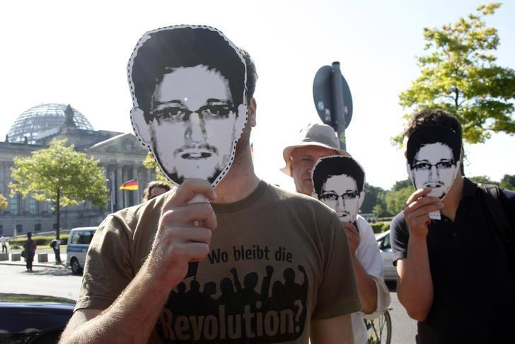 Protesters hold masks depicting former U.S. National Security Agency contractor Edward Snowden during a demonstration in Berlin May 22, 2014. The sentence on the shirt reads, ''What has happened to revolution''. REUTERS/Tobias Schwarz