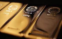 Слитки золота в магазине  Ginza Tanaka в Токио 18 апреля 2013 года. Цены на золото стабилизировались в среду, так как неприятие риска из-за Украины, где бои могут ужесточиться, компенсировали эффект от укрепления доллара. REUTERS/Yuya Shino