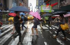 People cross the road in the rain at Times Square in New York June 9, 2014.     REUTERS/Carlo Allegri