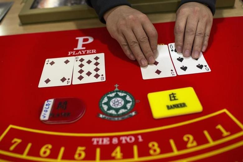A student displays a deck of cards on a gaming table during a gaming lesson at a mock casino run by the Macao Polytechnic Institute (MPI) Gaming Teaching and Research Centre in Macau March 6, 2014. REUTERS/Tyrone Siu