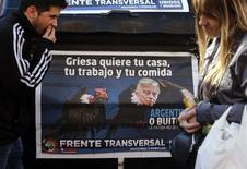 People walk past a poster depicting U.S. District Court for the Southern District of New York Judge Thomas Griesa as a vulture in Buenos Aires, August 12, 2014.    REUTERS/Marcos Brindicci