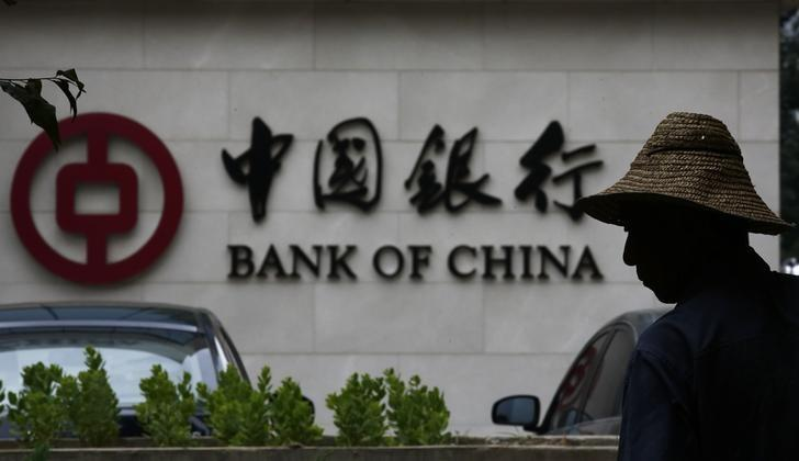 A man is silhouetted in front of a Bank of China's logo at its branch office in Beijing July 14, 2014.   REUTERS/Kim Kyung-Hoon