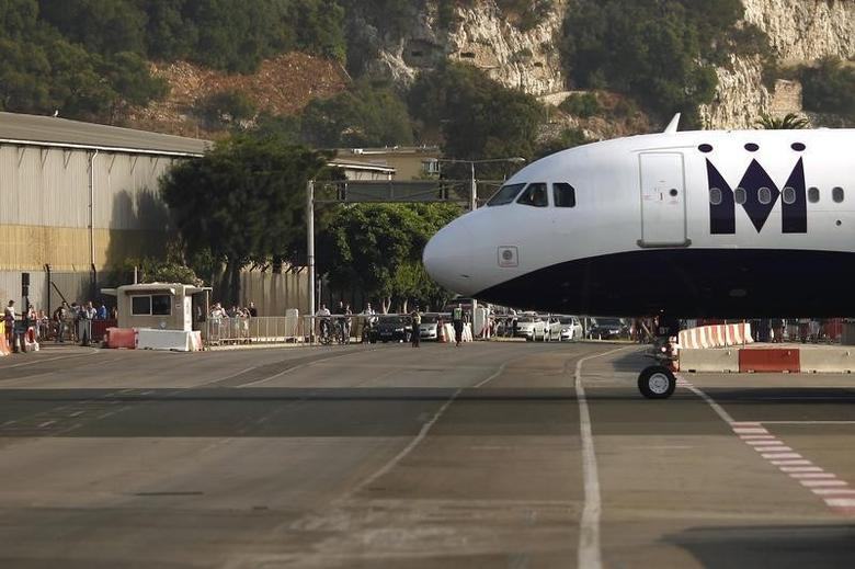 Pedestrians and drivers wait to cross the road of the Gibraltar International airport as a Monarch aircraft taxis on the tarmac after landing in Gibraltar, south of Spain August 5, 2013. REUTERS/Jon Nazca