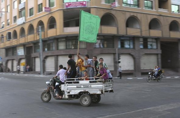 A Palestinian boy holding a Hamas flag rides in a motorbike rickshaw as they celebrate what they said was a victory over Israel, following a ceasefire in Gaza City August 26, 2014. REUTERS-Ahmed Zakot