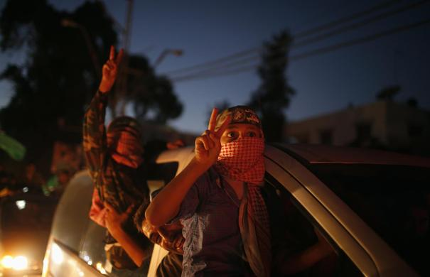 Masked Palestinian children wearing Hamas' armed wing headbands celebrate with others what they said was a victory over Israel, following a ceasefire in Gaza City August 26, 2014.REUTERS-Mohammed Salem