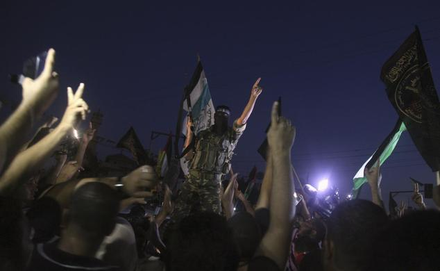 A Palestinian militant celebrates with people what they said was a victory over Israel, following a ceasefire in Gaza City August 26, 2014. REUTERS-Majdi Fathi
