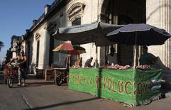 Unos vendedores de carne de cerdo en una calle de La Habana, jul 6 2014. Cuba puso en vigor el lunes reglas más estrictas sobre los artículos de consumo que viajeros pueden ingresar al país y aumentó sus aranceles, en un ajuste en las regulaciones que irritó a ciudadanos acostumbrados a contrarrestar la escasez crónica de productos en la isla con compras en el exterior. REUTERS/Stringer