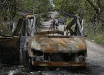 Сгоревший автомобиль в селе Семеновка 13 июля 2014 года. Российские власти объявили о гибели фотографа Андрея Стенина, пропавшего в начале августа на востоке Украины. REUTERS/Gleb Garanich