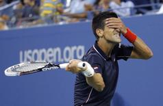 Novak Djokovic of Serbia makes fun of himself after missing a shot to Andy Murray of Britain during their quarter-final men's singles match at the 2014 U.S. Open tennis tournament in New York early on September 4, 2014.  REUTERS/Ray Stubblebine