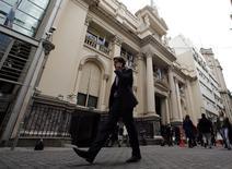 Un hombre habla por teléfono mientras pasa frente a la sede del Banco Central de Argentina en  Buenos Aires. 31 de julio de 2014. El Banco Central de Argentina informó el domingo que avanzó en un acuerdo de intercambio de monedas con su par de China, que le permitiría recibir 1.000 millones de dólares este año. REUTERS/Marcos Brindicci
