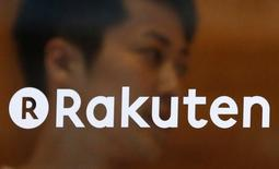 A staff of Rakuten Cafe is seen behind a logo of Rakuten Inc. at a shopping district in Tokyo August 4, 2014. REUTERS/Yuya Shino