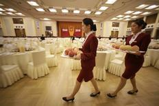 Attendants carry trays of peaches as they prepare for a reception marking the 61th anniversary of China at the Great Hall of the People in Beijing in this September 30, 2010 file photo. REUTERS/Jason Lee/Files