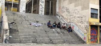 Unos vagabundos descanzando en las escaleras de un edificio en Belo Horizonte, Brasil, jun 17 2014. La concentración de la renta en Brasil aumentó levemente el año pasado por primera vez desde el 2004, mientras que la tasa de desempleo volvió a subir debido a una insuficiente apertura de puestos de trabajo, mostró el jueves la Encuesta Nacional de Hogares.  REUTERS/Michael Dalder