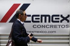 Una persona pasa frente al logo de la empresa mexicana Cemex en Ciudad de México. Imagen de archivo, 27 agosto, 2014. La mexicana Cemex, una de las mayores cementeras del mundo, dijo el martes que obtuvo un nuevo crédito bancario por 1,350 millones de dólares, que mejora las condiciones establecidas en su actual acuerdo financiero y que utilizará para refinanciar deuda. REUTERS/Edgard Garrido