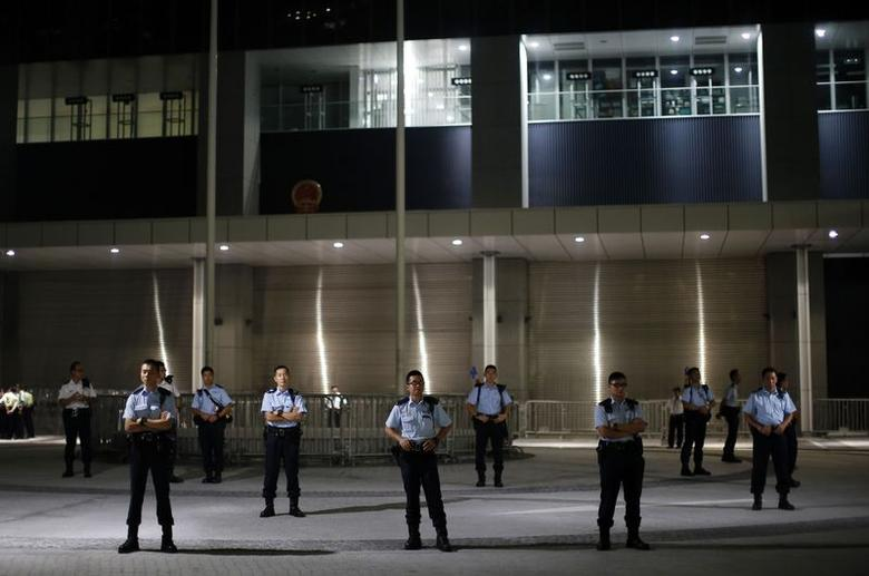 Police officers guard the entrance of the government headquarters building as protesters block the nearby areas in Hong Kong, September 30, 2014. REUTERS/Carlos Barria