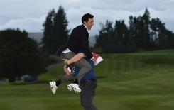 "Team Europe golfer Rory McIlroy is lifted up by a colleague after the closing ceremony of the 40th Ryder Cup at Gleneagles in Scotland September 28, 2014. Captain Paul McGinley described each of his players as ""a colossus"" after holders Europe won the Ryder Cup for the eighth time in 10 editions on Sunday.           REUTERS/Toby Melville (BRITAIN  - Tags: SPORT GOLF)"
