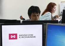 Сотрудники Московской биржи за работой 3 июня 2014 года. Российские фондовые индексы открыли торги понедельника повышением, восстанавливаясь вторую сессию, несмотря на дешевеющий рубль. REUTERS/Sergei Karpukhin