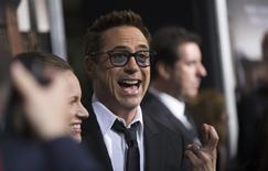 """Cast member Robert Downey Jr. crosses his fingers as he poses with his wife and producer of the movie Susan Downey at the premiere of """"The Judge"""" at the Academy of Motion Picture Arts and Sciences in Beverly Hills, California October 1, 2014. REUTERS/Mario Anzuoni"""