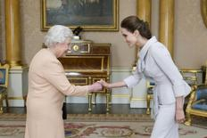 Actress Angelina Jolie is greeted by Britain's Queen Elizabeth before being presented with the Insignia of an Honorary Dame Grand Cross of the Most Distinguished Order of St Michael and St George, in the 1844 room at Buckingham Palace in London October 10, 2014.   REUTERS/Anthony Devlin