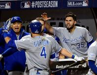 Oct 10, 2014; Baltimore, MD, USA; Kansas City Royals left fielder Alex Gordon (4) is greeted in the dugout after he hit a solo home run in the 10th inning against the Baltimore Orioles in game one of the 2014 ALCS playoff baseball game at Oriole Park at Camden Yards. Tommy Gilligan-USA TODAY Sports