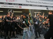 Mercedes Formula One team members spray champagne on Mercedes Formula One driver Lewis Hamilton of Britain after winning the 2014 constructors World Championship at the first Russian Grand Prix in Sochi October 12, 2014. REUTERS/Maxim Shemetov