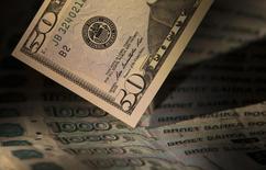 Купюры валют доллар США и рубль в Москве 17 февраля 2014 года. Российская валюта утром среды достигла новых абсолютных минимумов, а доллар преодолел психологическую отметку в 41 рубль из-за дефицита валюты при ограничении доступа к западным ресурсам и на фоне глубокого падения нефтяных цен. REUTERS/Maxim Shemetov